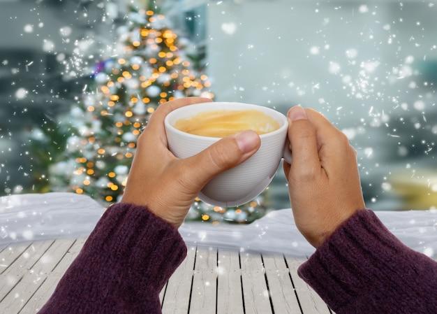 Mano sujetando café de invierno, navidad blanca con nieve en segundo plano.