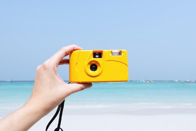 Mano sujetando la cámara amarilla sobre fondo de playa de verano