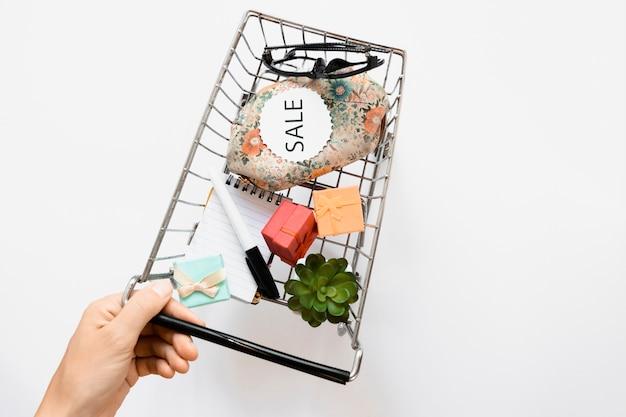 Mano sujetando el carrito de compras con etiqueta de venta
