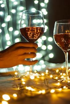 Mano sujetando una copa de vino transparente