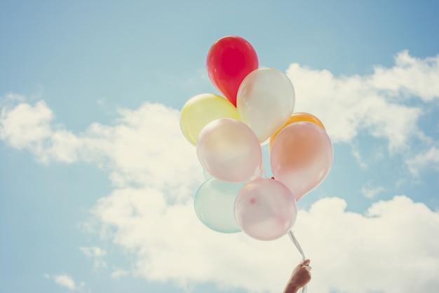 Mano sujetando globos de diferentes colores