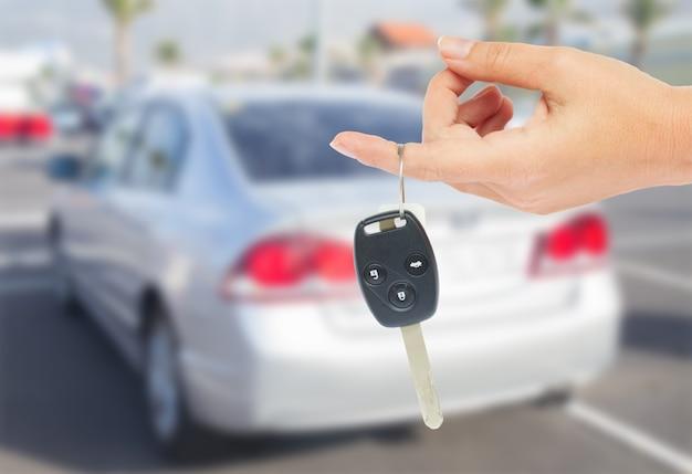Mano sujetando una llave de coche con coche metálico en el fondo