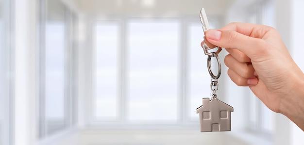 Mano sujetando la llave para la nueva casa interior de nueva construcción - imagen