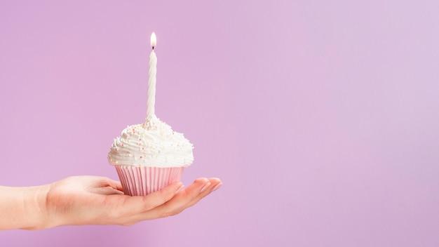 Mano sujetando muffins de cumpleaños sobre fondo rosa