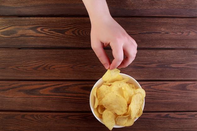 Mano sujetando papas fritas en un plato aislado sobre fondo de madera
