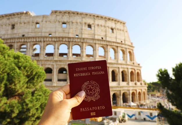 Mano sujetando el pasaporte italiano frente al coliseo de roma