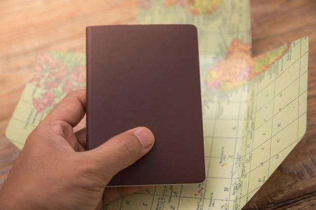 Mano sujetando un pasaporte con un mapa del mundo detrás