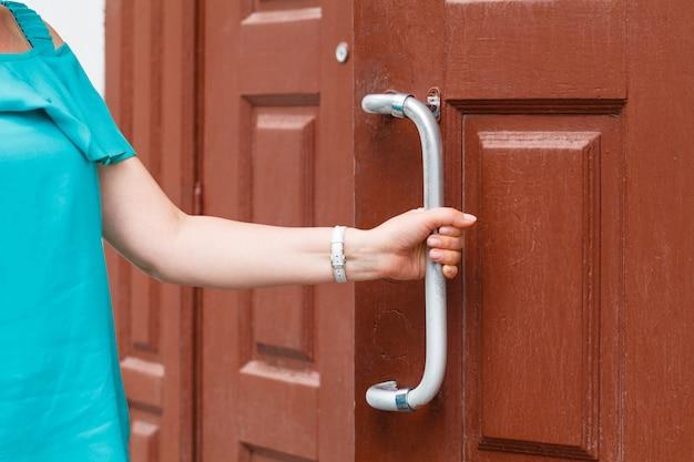 Mano sujetando la perilla de la puerta, abriendo la puerta ligeramente, enfoque selectivo