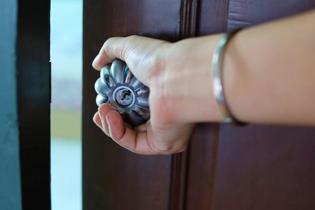 Mano sujetando el pomo de la puerta metálica