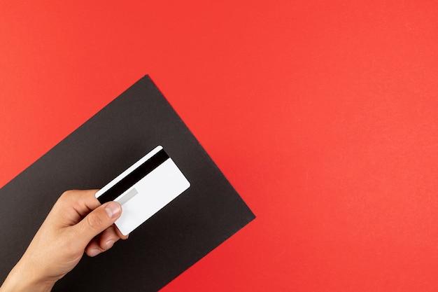Mano sujetando una tarjeta de crédito sobre fondo rojo.