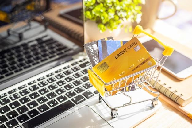 Mano sujetando tarjetas de crédito con una computadora portátil y un teléfono móvil