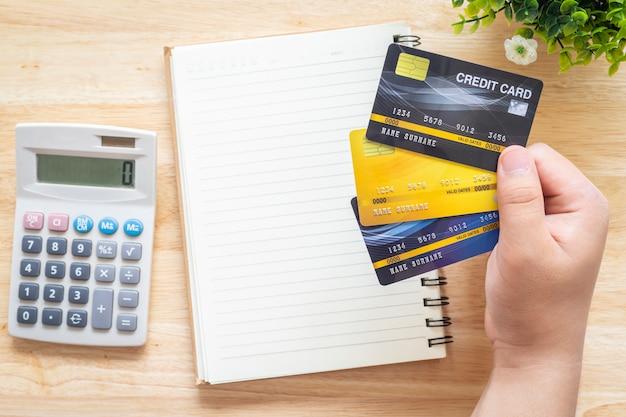 Mano sujetando tarjetas de crédito con un cuaderno y una calculadora