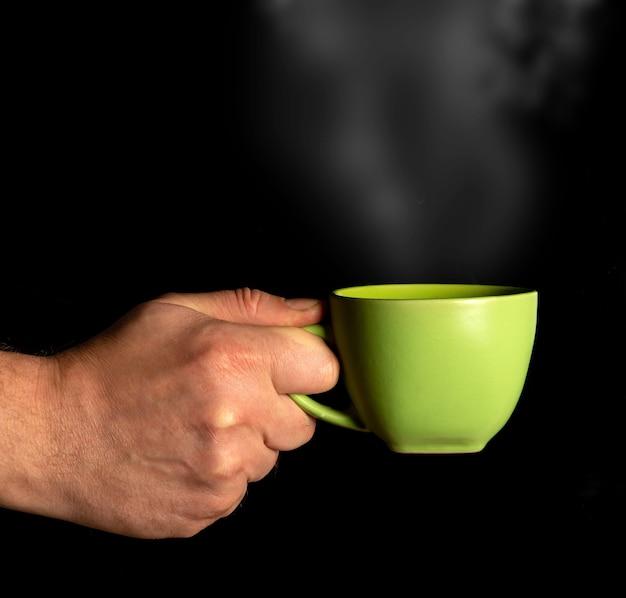 Mano sujetando la taza con vapor de cerca