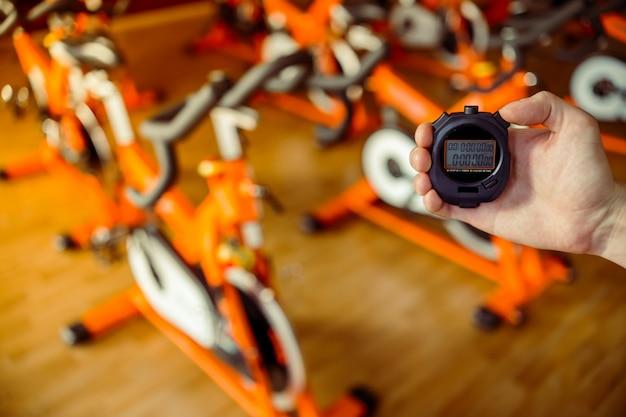 Mano sujetando un temporizador, filas de bicicletas estáticas en el gimnasio