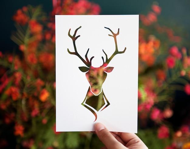 Mano sujetar ciervos con astas talla de papel