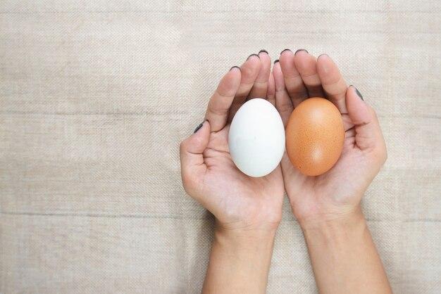 Mano superior de la visión de mujeres asiáticas jovenes, sosteniendo los huevos blancos y amarillos.