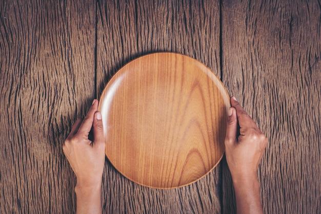 Mano superior de la visión que sostiene la placa en el fondo de madera