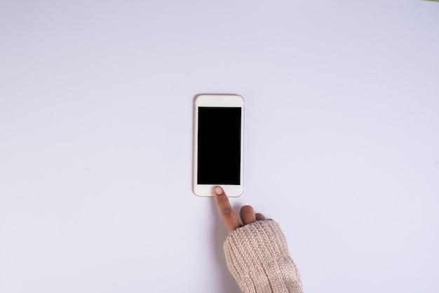 Mano superior vista sosteniendo teléfono celular sobre fondo blanco
