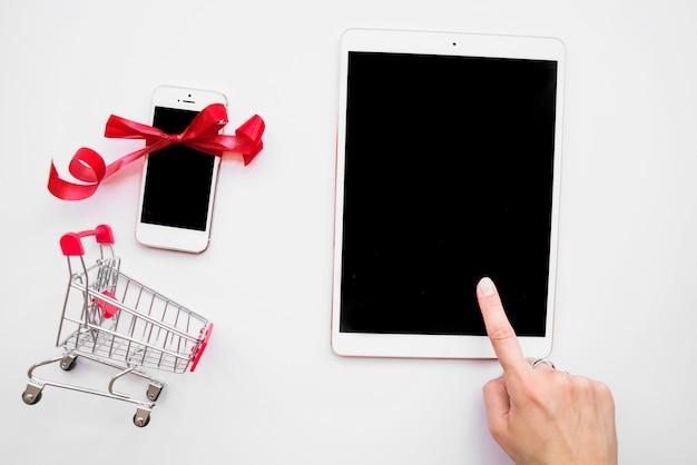 Mano en tableta cerca de teléfono inteligente y carrito de compras