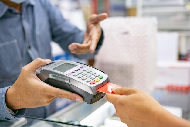 Mano con tarjeta de crédito deslizar máquina para pagar