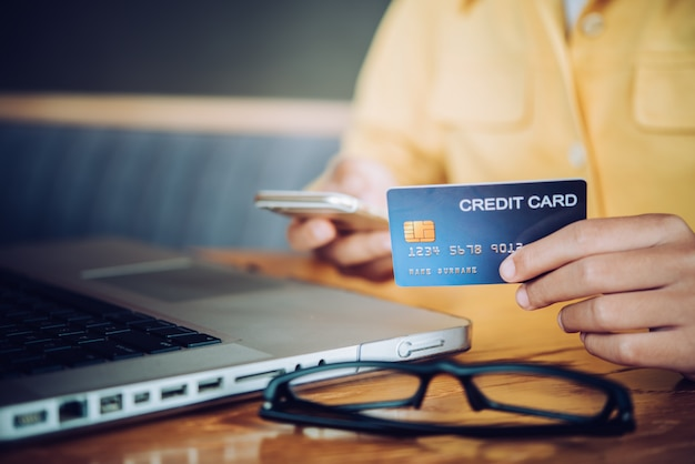 De la mano con una tarjeta de crédito en sus manos y encuentre información sobre un producto usando su dispositivo portátil para realizar compras en línea y realizar transacciones financieras.