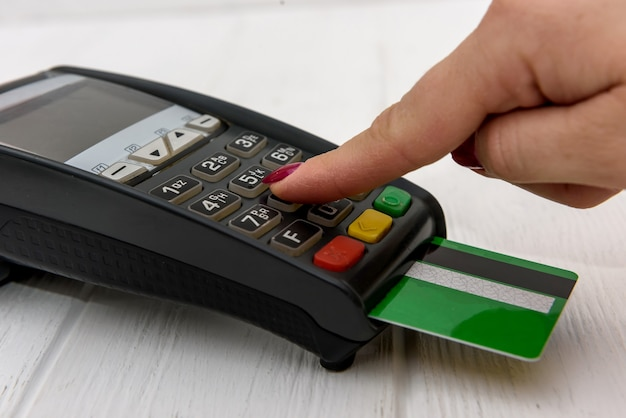 Mano con tarjeta de crédito y terminal bancario