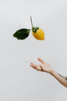 Mano tatuada arrojando un limón en un cielo gris