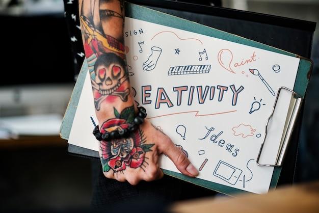 Mano tatuada sosteniendo un portapapeles de creatividad.