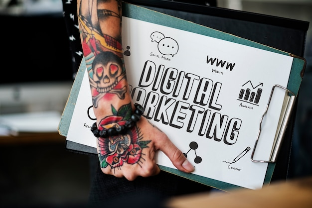 Mano tatuada sosteniendo un portapapeles de marketing digital.