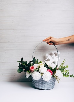Mano con el tatuaje que sostiene la cesta de flores frescas en el escritorio blanco contra el papel pintado de madera