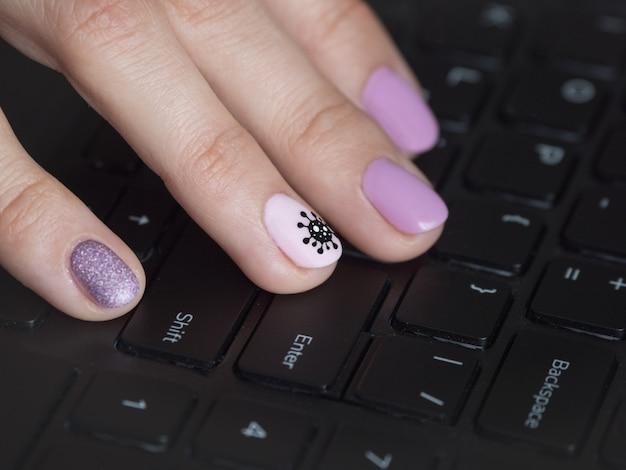 La mano en el teclado. manicura creativa con coronavirus pintado en las uñas.