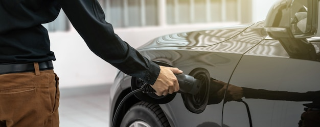 La mano de un técnico asiático de primer plano está cargando el auto eléctrico o ev en el centro de servicio