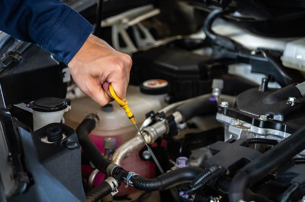 Mano del técnico comprobando el nivel de aceite en la varilla medidora en el motor del automóvil