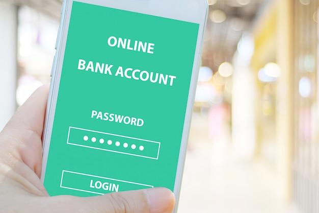 Mano con teléfono inteligente con inicio de sesión de contraseña de cuenta bancaria en línea en la pantalla desenfoque de fondo