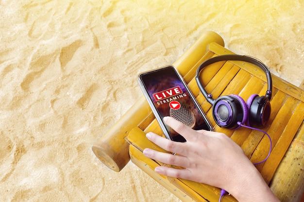 Mano en el teléfono móvil con transmisión de música en vivo y auriculares, música en viaje