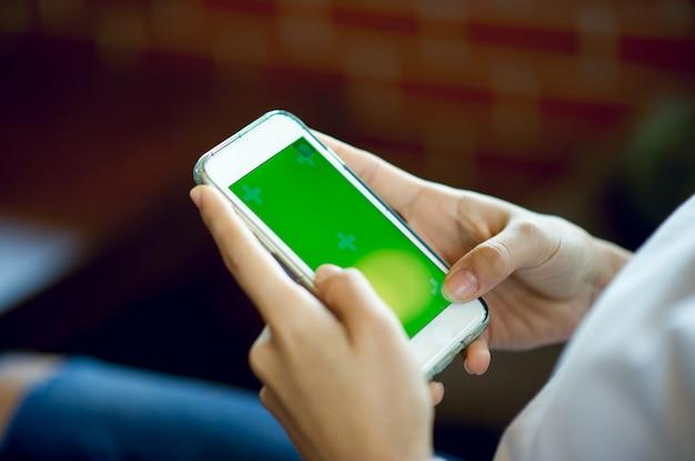 Mano y teléfono de la muchacha que hace negocio en línea y concepto de la comunicación empresarial con el espacio de la copia.