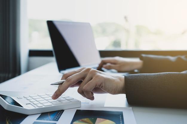 La mano del tenedor de libros de las empresarias utiliza la calculadora y la computadora portátil en el escritorio blanco en la oficina de trabajo.