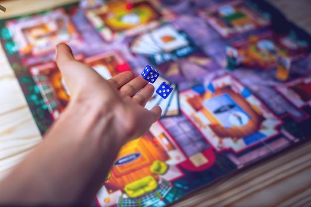 La mano tira los dados en el juego de mesa