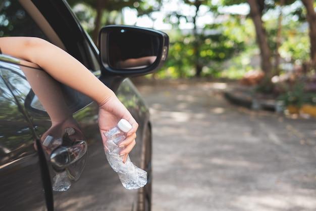 Mano tirando botella de plástico en la carretera.