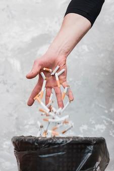 Mano tirando cigarrillos en la basura contra la pared vieja