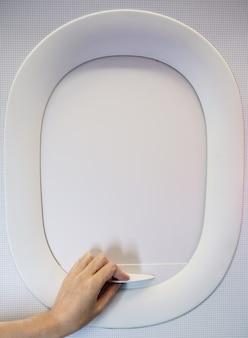 Mano tirando hacia abajo o hacia arriba de la cortina de la ventana del avión mientras viaja en vuelo.