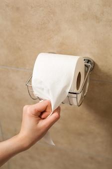 Mano tirando del rollo de papel higiénico en el soporte