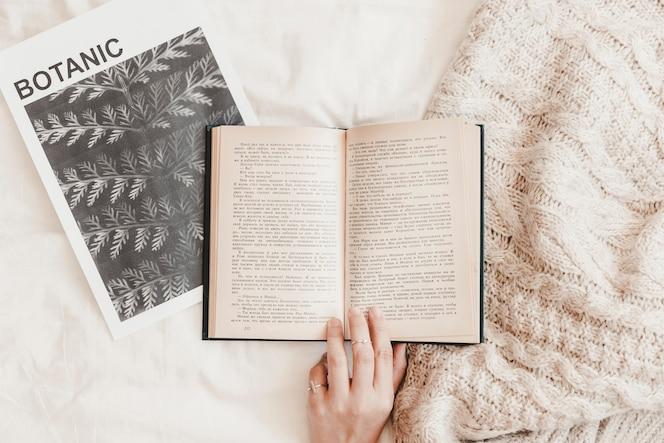 Mano tocando el libro en el cartel y la manta en la sábana