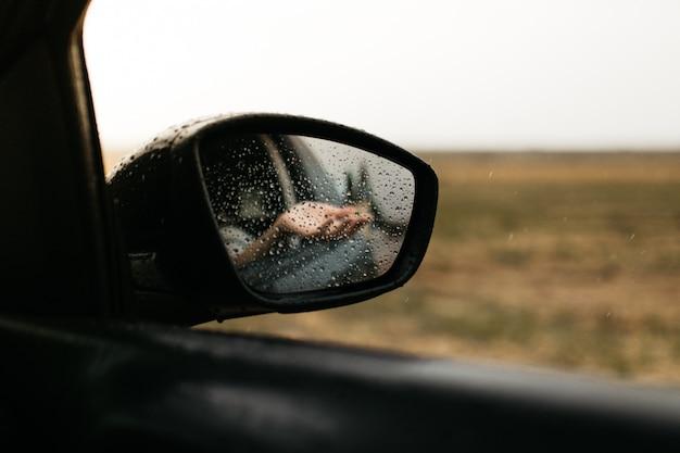 Mano tocando gotas de lluvia. espejo visto a través del cristal. ventana de coche mojada. ciérrese encima de la gota de lluvia. vista del coche ver el espejo. día lluvioso.
