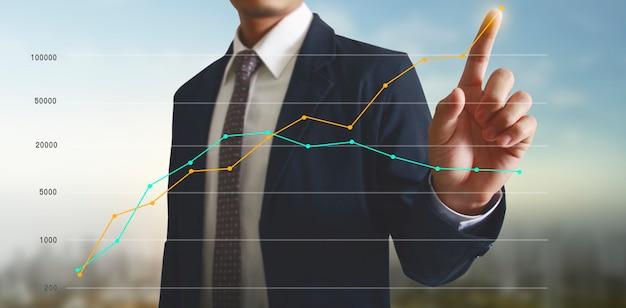 Mano tocando un gráfico del indicador financiero y la tabla de análisis de economía de mercado contable
