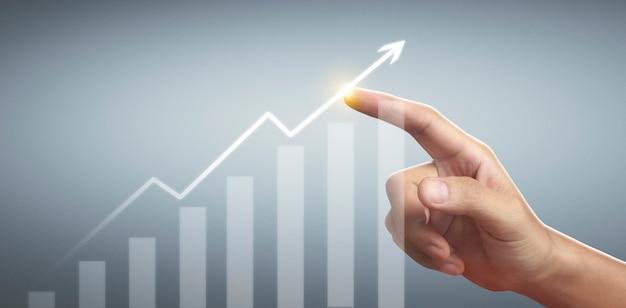 Mano tocando gráficos de indicador financiero y gráfico de análisis de economía de mercado contable
