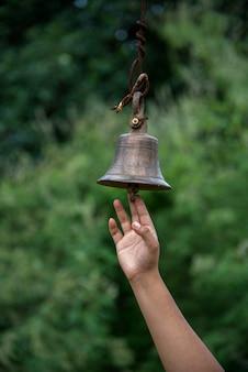 Mano tocando una gran campana en el templo. al aire libre