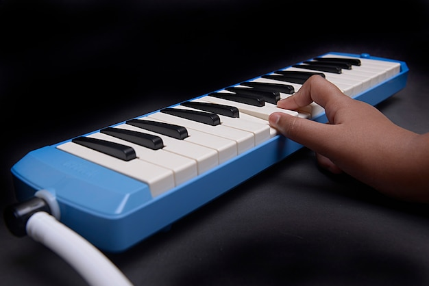 Mano tocando instrumento musical pianica blow-organ con fondo negro