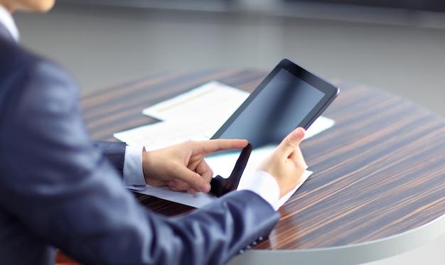 Mano tocando en el moderno tablet pc digital en el lugar de trabajo.