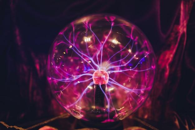 Mano tocando plasmball con suaves llamas azul magenta.